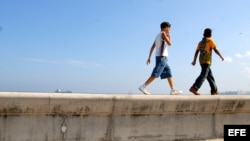 Dos niños caminan por el malecón de La Habana.