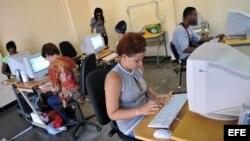 """Varias personas consultan Intranet en una """"sala de navegación"""", perteneciente a la empresa estatal Correos de Cuba."""