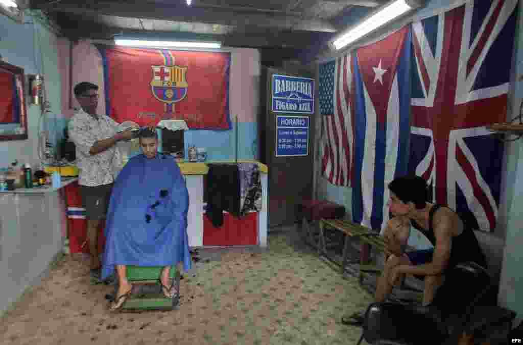 Banderas de EE UU, Reino Unido y Cuba en una barbería de La Habana.