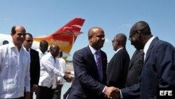 """El primer ministro de Haití, Laurent Salvador Lamothe (c), saluda a varios oficiales cubanos acompañado por el vicecanciller de Cuba, Rogelio Sierra (i), a su llegada al aeropuerto habanero """"José Martí"""" de La Habana (Cuba)"""