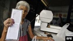 Archivo: Una anciana muestra su libreta de racionamiento en Cuba
