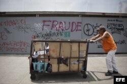 """Un hombre empuja un carrito frente a un muro con una pintada en donde se lee """"fraude"""" hoy, miércoles 17 de abril de 2013, escrito como una protesta contra el presidente venezolano, Nicolás Maduro y el resultado electoral que le dio como vencedor en Caraca"""