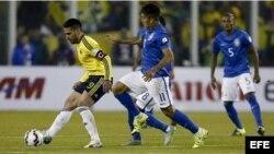 El delantero colombiano Radamel Falcao (i) controla el balón junto al centrocampista brasileño Roberto Firmino (c).