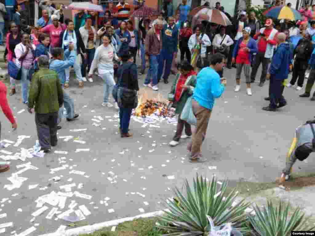 Las Brigadas de Respuesta Rápida queman ejemplares de la Declaración Universal de los Derechos Humanos, lanzados a la calle por las damas de Blanco. Foto cortesía Ángel Moya.