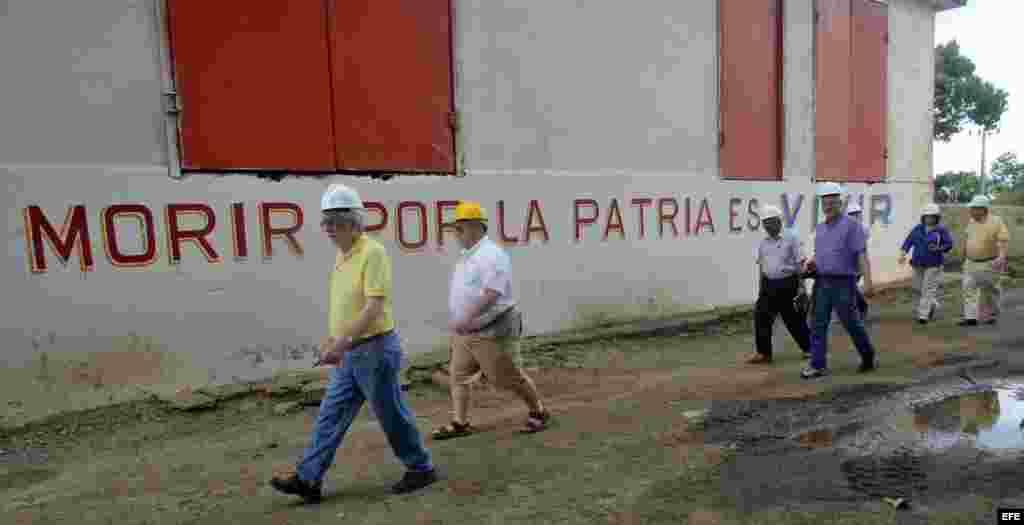 Empresarios del sector agrícola de Estados Unidos paseando frente a un mural con estrofas del himno nacional cubano.