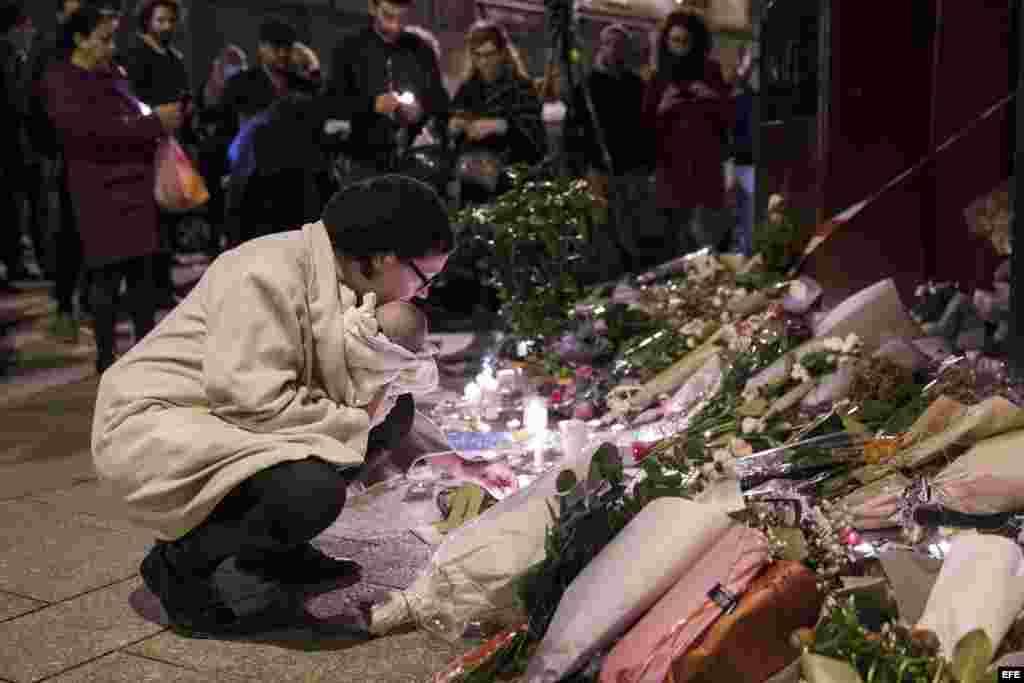 Una mujer rinde tributo a las víctimas frente al café Carillon, uno de los seis sitios atacados por los terroristas de Estado Islámico en París. EFE