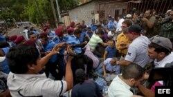 Un grupo de personas forcejea con un grupo de policías , a las afueras de la sede del Instituto Nicaragüense de Seguridad Social (INSS) en Managua, Nicaragua