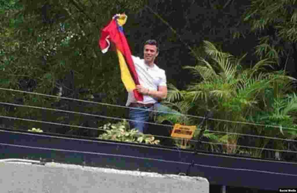 Luciendo una camiseta blanca, un sonriente Leopoldo López levantó las manos en señal de victoria, desde el jardín de su casa, en medio de la ovación de decenas de simpatizantes que lo esperaban afuera.