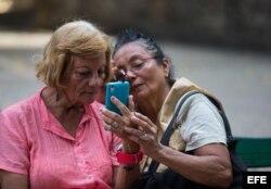 Aída Puppo (i), de 71 años, habla en video conferencia con su hijo que vive desde hace 20 años en Estados Unidos, al aprovechar una señal de internet en una plaza de Centro Habana en marzo de 2016, en La Habana.