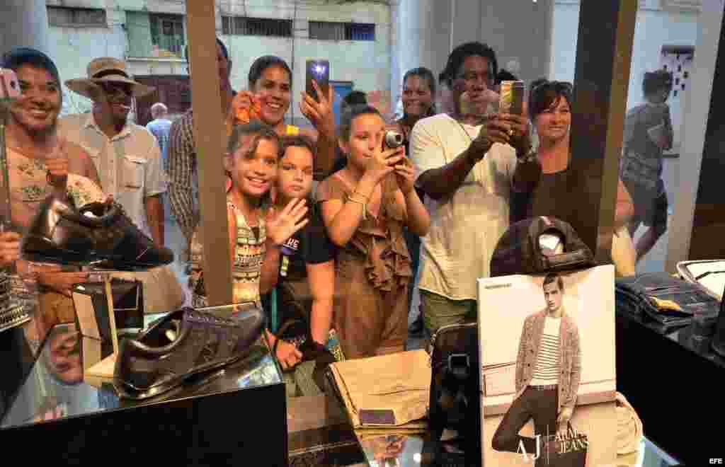 Varias personas observan el interior de una de las nuevas tiendas de lujo inauguradas este sábado en La Habana.