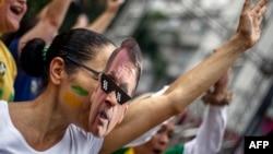 Una manifestante con una máscara de Bolsonaro apoya al candidato ultraderechista en Sao Paulo.