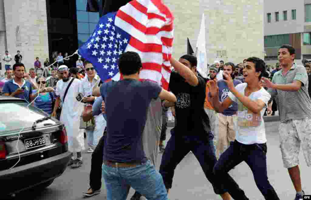 Unos manifestantes rompen una bandera estadounidense durante una concentración frente a la Embajada de Estados Unidos en Túnez (Túnez) en protesta contra un vídeo realizado por Sam Bacile, un israelí-estadounidense, en el que se critica el islam y se cari