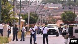 Policías ministeriales resguardan la zona donde fueron asesinadas once personas el viernes 3 de agosto de 2018, en Ciudad Juárez, Chihuahua (México)