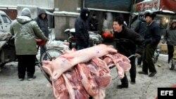 Un vendedor carga una carretilla con carne de cerdo para vender en un mercado de Shenyang, China.