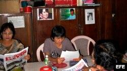 Archivo - Miembros de la Liga Nacional para la Democracia leen el periódico bajo un retrato de la líder opositora Aung San Suu Kyi en la sede del partido, en Rangún (Birmania).
