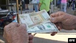 Un hombre muestra un peso convertible cubano y un dólar estadounidense. (Archivo)