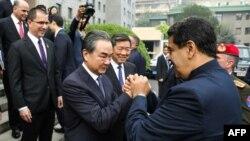 El presidente venezolano Nicolás Maduro (D) y el ministro chino de Exteriores Wang Yi se saludan, en Pekín el 14 de septiembre de 2018, en una imagen transmitida por la presidencia venezolana© Venezuelan Presidency/AFP MARCELO GARCIA