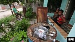 """Varias personas permanecen junto a botellas de ron vacías en una vivienda del barrio Alturas de la Lisa en La Habana donde hace pocos días se produjo un caso de intoxicación con alcohol metílico o """"de madera"""" comercializado ilegalmente."""