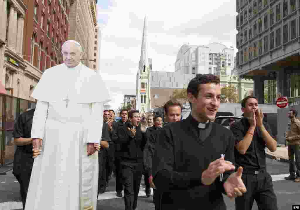 Seminaristas católicos marchan por las calles de Filadelfia junto a una imagen gigante del Papa.