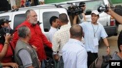 El periodista Mario Silva (con camisa roja) es asediado por la prensa tras estallar el escándalo.