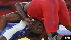 Archivo - El luchador cubano Livan Lopez Azcuy (rojo) se enfrenta al canadiense Haislan Veranes Garcia (azul) en Londres.