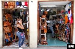 Una mujer habla por teléfono frente a dos negocios privados de venta de artesanías en La Habana (Cuba).