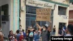 Joven con cartel protesta en el bulevar de San Rafael, La Habana