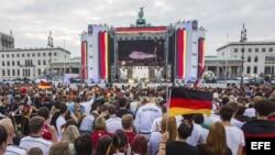 """Simpatizantes de la selección nacional alemana de fútbol siguen por televisión la salida de los jugadores de Brasil en la llamada """"Milla del aficionado"""" en la Puerta de Brandeburgo en Berlín (Alemania)."""