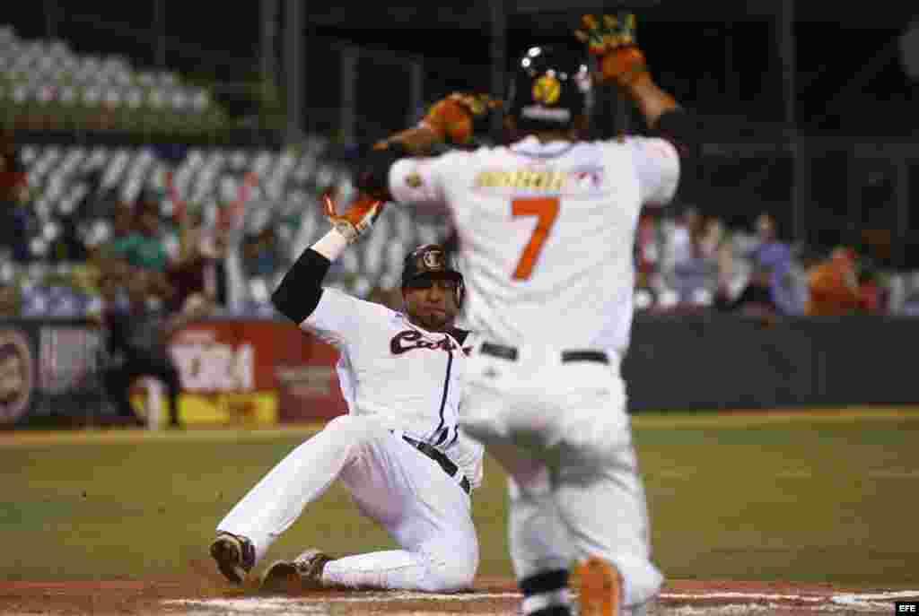 El jugador venezolano Jose Castillo (atrás) en acción durante la semifinal entre Cuba y Venezuela por la Serie del Caribe de Béisbol,