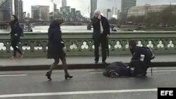 Captura de vídeo que muestra a varias personas mientras atienden a un herido tras un tiroteo en el Wetminster Bridge junto al Parlamento en Londres, Reino Unido, hoy, 22 de marzo de 2017.