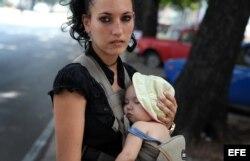 Una mujer carga a su pequeño hijo en La Habana, agosto de 2014.