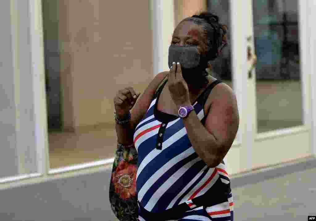 Una mujer cubana con una máscara protectora camina por una calle de La Habana.