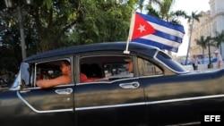 Un viejo taxi con una bandera cubana.