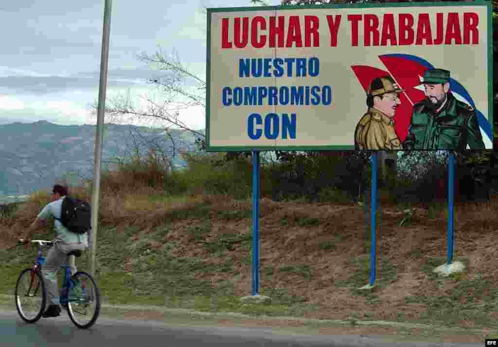 Un hombre pasa en bicicleta junto a un cartel con la foto de Fidel Castro en la provincia de Guantánamo, Cuba.