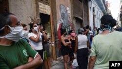 Cubanos se protegen con máscaras durante la espera para comprar en una tienda en La Habana.