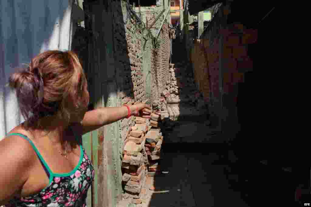 Una mujer señala un muro a punto de caer de un callejón desplomado hoy, lunes 18 de abril de 2016, tras un fuerte sismo de 7,8 grados que sacudió al país en la zona hotelera de Tarqui en Manta (Ecuador).