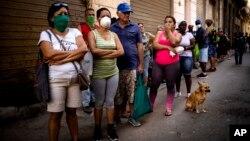 Cubanos hacen fila para comprar alimentos.