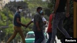 Un agente vestido de civil detiene el martes a un hombre en el lugar donde estaba previsto que se hiciera la protesta (Alexandre Meneghini/Reuters).