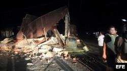 Un grupo de personas permanece a las afueras de una casa destruida en la localidad de Nagarote, 30 kilómetros al occidente de Managua.