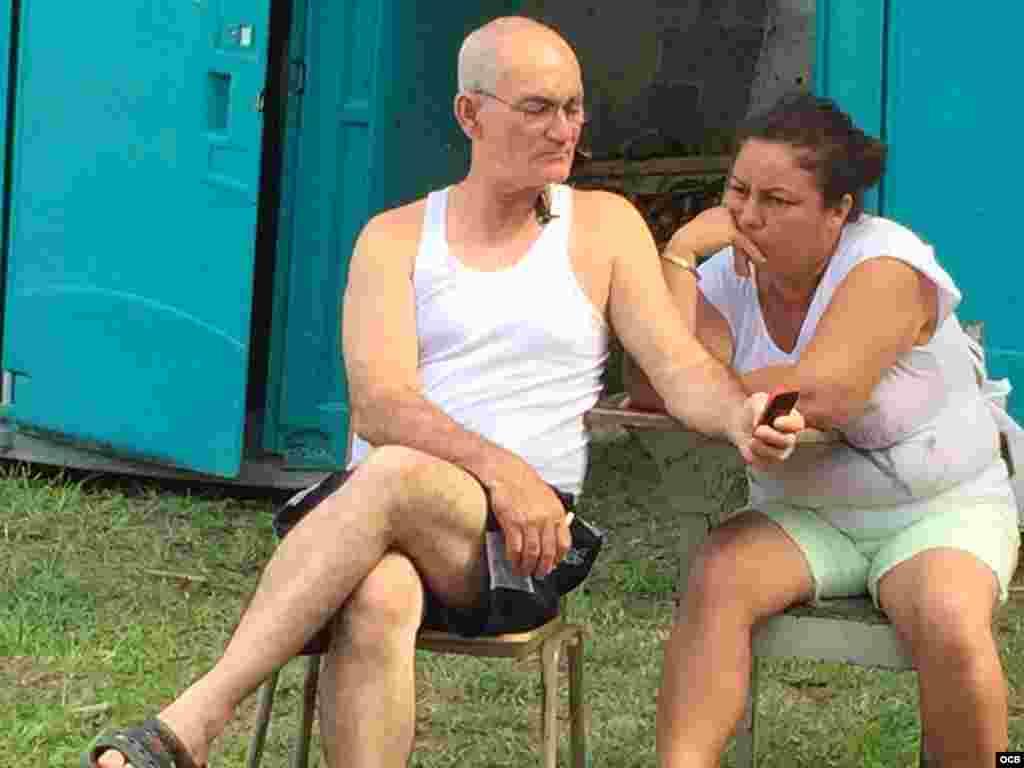 Cubanos revisando mensajes en su celular en uno de los albergues en Costa Rica. Fotos: Claudio Castillo, Martí Noticias.