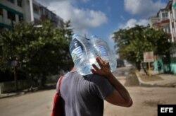 Un hombre camina con dos bidones de agua potable en uno de los barrios afectados por el paso del huracán Irma en La Habana.
