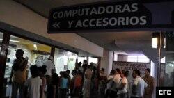 Varias personas hacen cola para comprar computadoras, o simplemente curiosear, en una tienda de La Habana.