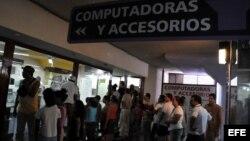 Varias personas hacen cola para comprar computadoras, o simplemente curiosear en una tienda de La Habana.