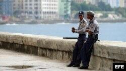 Dos policías descansan en el muro del malecón habanero.