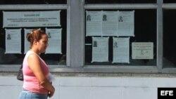 Una mujer camina junto a carteles alusivos a las elecciones de los delegados a las asambleas nacionales y provinciales del Poder Popular en Cuba.