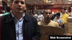 Eliécer Ávila (izquierda) protesta junto a otros miembros de Somos+ en el Aeropuerto Internacional José Martí, de La Habana.