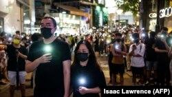 Residentes de Hong Kong rinden homenaje a los muertos de Tiananmén, el 4 de junio de 2021. (Isaac Lawrence / AFP).