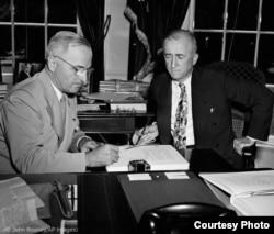 El presidente Harry Truman (izda.) firma la carta de la ONU para completar su ratificación, mientras el secretario de Estado James Byrnes observa. (© John Rooney/AP Images)