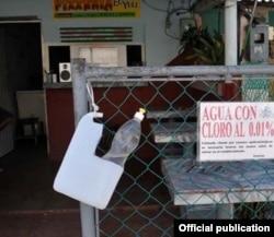 """Un recipiente con agua mezclada con cloro al 0.01 por ciento en la entrada de un establecimiento de Isla de la Juventud, en una foto del diario local """"Victoria""""."""