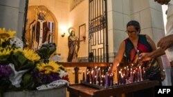 Peregrinos encienden velas a San Lázaro, en El Rincón, La Habana.